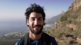 Ritratto del primo piano della viandante maschio sorridente sulla montagna stock footage