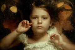 Ritratto del primo piano di autunno di piccola ragazza caucasica, attraverso gocce di acqua Immagini Stock