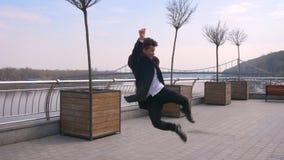 Ritratto del primo piano di ballare di camminata del giovane uomo d'affari afroamericano attraente e di salto felicemente sulla v stock footage