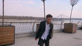 Ritratto del primo piano di ballare di camminata del giovane uomo d'affari afroamericano felice esaminando macchina fotografica e archivi video