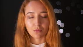 Ritratto del primo piano di bella condizione della donna dello zenzero isolato su fondo nero e sull'esame tranquillamente la macc archivi video