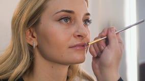Ritratto del primo piano di bella donna bionda che fa trucco sulle sue labbra fotografie stock