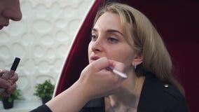 Ritratto del primo piano di bella donna bionda che fa trucco sulle sue labbra stock footage