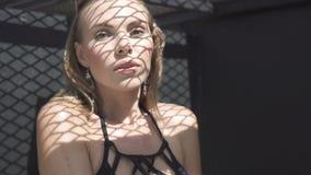 Ritratto del primo piano di bella donna bionda che indossa swimwear nero che si siede su un tetto in un giorno di estate soleggia stock footage