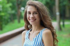 Ritratto del primo piano di bella donna in vestito da estate che posa nel parco verde che gode del fine settimana Ragazza caucasi Fotografie Stock