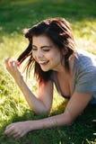 Ritratto del primo piano di bella giovane donna caucasica sorridente con capelli neri rossi, trovandosi sull'erba all'aperto, rid Fotografia Stock Libera da Diritti
