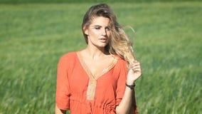 Ritratto del primo piano di bella giovane donna romantica bionda in una camicia rossa che tocca i suoi capelli al campo verde stock footage