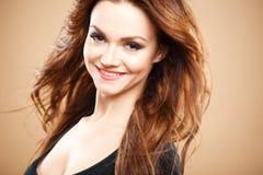 Ritratto del primo piano di bella giovane donna sexy con capelli marroni lunghi sopra fondo marrone Fotografie Stock Libere da Diritti
