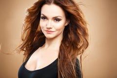 Ritratto del primo piano di bella giovane donna sexy con capelli marroni lunghi sopra fondo marrone Immagine Stock