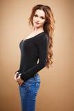 Ritratto del primo piano di bella giovane donna sexy con capelli marroni lunghi sopra fondo marrone Immagini Stock
