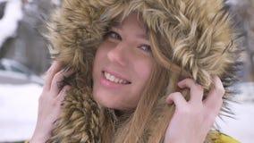 Ritratto del primo piano di bella giovane ragazza caucasica in cappuccio della pelliccia flirtingly che posa nella macchina fotog stock footage