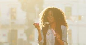 Ritratto del primo piano di bella ragazza afroamericana allegra con capelli ricci che soffiano le bolle di sapone durante il sole video d archivio