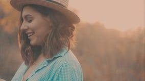 Ritratto del primo piano di bella ragazza con il cappello di paglia d'uso dei capelli scuri lunghi Gioca con i suoi capelli nel c video d archivio