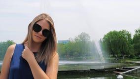 Ritratto del primo piano di bella ragazza in occhiali da sole con uno stile di capelli di modo nel parco vicino alla fontana cute archivi video