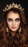 Ritratto del primo piano di bella ragazza in una corona e in un earrin dorati Immagini Stock Libere da Diritti