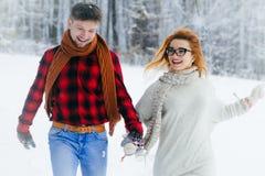 Ritratto del primo piano di belle coppie allegre che si tengono per mano e che corrono lungo la foresta nevosa Immagine Stock Libera da Diritti