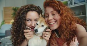 Ritratto del primo piano di belle ragazze e del cane che prendono selfie a casa che si trova sul letto stock footage