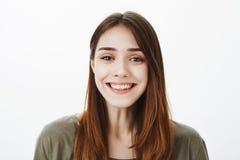 Ritratto del primo piano di castana europeo incantante amichevole con il vasto sorriso positivo, controllante fondo grigio fotografia stock