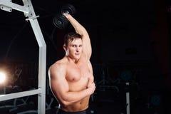Ritratto del primo piano di forte uomo muscolare di yang del culturista professionale che fa esercizio Allenamento con il bilanci Fotografia Stock