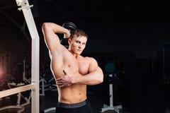 Ritratto del primo piano di forte uomo muscolare di yang del culturista professionale che fa esercizio Allenamento con il bilanci Fotografie Stock
