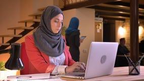 Ritratto del primo piano di giovane bella donna di affari musulmana nel hijab che scrive sul computer portatile all'interno sul p archivi video
