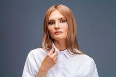 Ritratto del primo piano di giovane bella donna bionda in una camicia bianca immagine stock libera da diritti