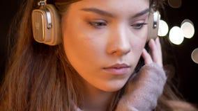Ritratto del primo piano di giovane bella ragazza caucasica in cuffie che ascolta attentamente la musica sulle luci vaghe archivi video