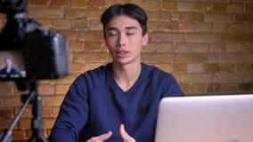 Ritratto del primo piano di giovane blogger maschio coreano che parla sulla macchina fotografica e che gesturing all'interno archivi video