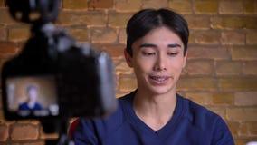 Ritratto del primo piano di giovane blogger maschio coreano che parla sulla macchina fotografica e sul ciao allegramente d'ondegg video d archivio