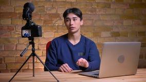 Ritratto del primo piano di giovane blogger maschio coreano che parla sulla macchina fotografica e sul ciao d'ondeggiamento con l video d archivio