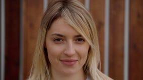Ritratto del primo piano di giovane donna allegra, esaminante macchina fotografica sulla via stock footage