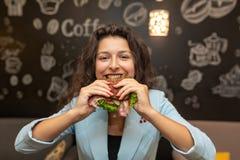 Ritratto del primo piano di giovane donna caucasica affamata, panino del morso fotografie stock libere da diritti