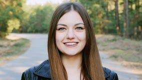 Ritratto del primo piano di giovane donna graziosa, sorridente ed esaminante macchina fotografica al rallentatore archivi video