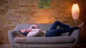 Ritratto del primo piano di giovane femmina castana caucasica attraente che ha una menzogne di telefonata rilassata sullo strato  stock footage
