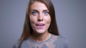 Ritratto del primo piano di giovane femmina caucasica allegra che è sorridere sorpreso ed esaminare macchina fotografica stock footage