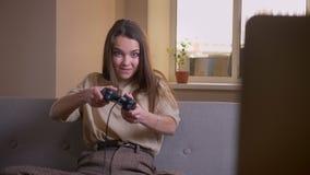 Ritratto del primo piano di giovane femmina caucasica attraente che gioca i video giochi e che ottiene felice celebrando seduta s archivi video