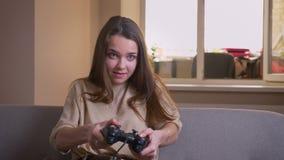 Ritratto del primo piano di giovane femmina caucasica attraente che gioca i video giochi che si siedono felicemente sullo strato  archivi video