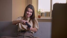 Ritratto del primo piano di giovane femmina caucasica attraente che gioca i video giochi che vengono a mancare e che ottengono se archivi video