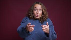 Ritratto del primo piano di giovane femmina caucasica che ottiene gesturing sorpreso ed eccitato e gridare mentre esaminando macc video d archivio