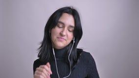 Ritratto del primo piano di giovane femmina caucasica graziosa nelle vibrazioni che ballano e che ascoltano la musica davanti all video d archivio
