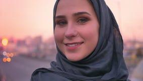 Ritratto del primo piano di giovane femmina musulmana attraente nel hijab che sorride allegramente e che esamina diritto la macch stock footage