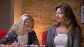 Ritratto del primo piano di giovane madre caucasica e sua piccola della figlia graziosa che spendono insieme tempo Ragazza osserv archivi video