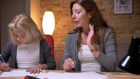 Ritratto del primo piano di giovane madre e della figlia che riuniscono Mamma preoccupantesi che ripara i capelli ed il disegno d archivi video