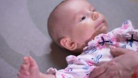 Ritratto del primo piano di giovane mano della madre con le sue bugie neonate sveglie della figlia sul sofà e sugli orologi right stock footage