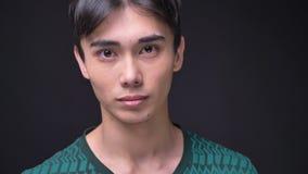 Ritratto del primo piano di giovane maschio coreano attraente che gira dal lato che esamina macchina fotografica e sorridere video d archivio