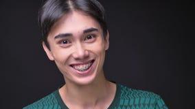 Ritratto del primo piano di giovane maschio coreano attraente che ottiene sorpreso ed eccitato mentre esaminando macchina fotogra video d archivio