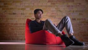 Ritratto del primo piano di giovane maschio coreano che gioca con indifferenza i video giochi mentre sedendosi nella borsa di fag video d archivio