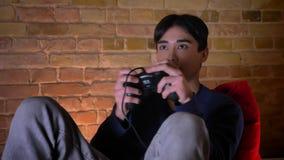 Ritratto del primo piano di giovane maschio coreano che gioca i video giochi e che si eccita mentre sedendosi sulla borsa di fagi video d archivio