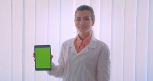 Ritratto del primo piano di giovane medico femminile caucasico attraente che tiene un tabletand che mostra ad intensità verde sch video d archivio