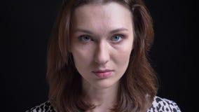 Ritratto del primo piano di giovane modello femminile caucasico grazioso che esamina diritto la macchina fotografica con i bei oc archivi video
